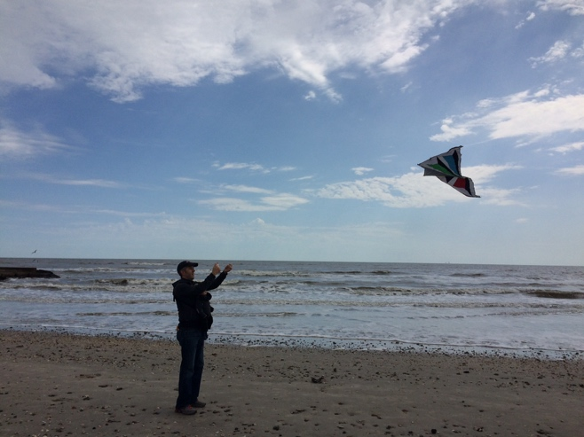 Man and baby flying a kite on the beach