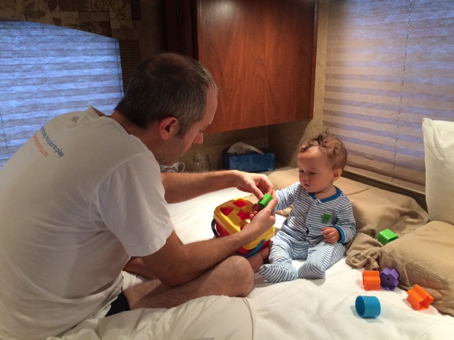 Dad and baby playing with blocks in bed