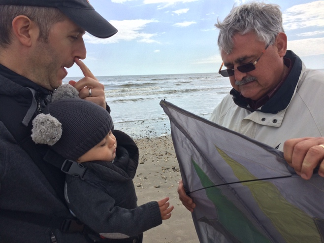 Two men and baby assembling kite