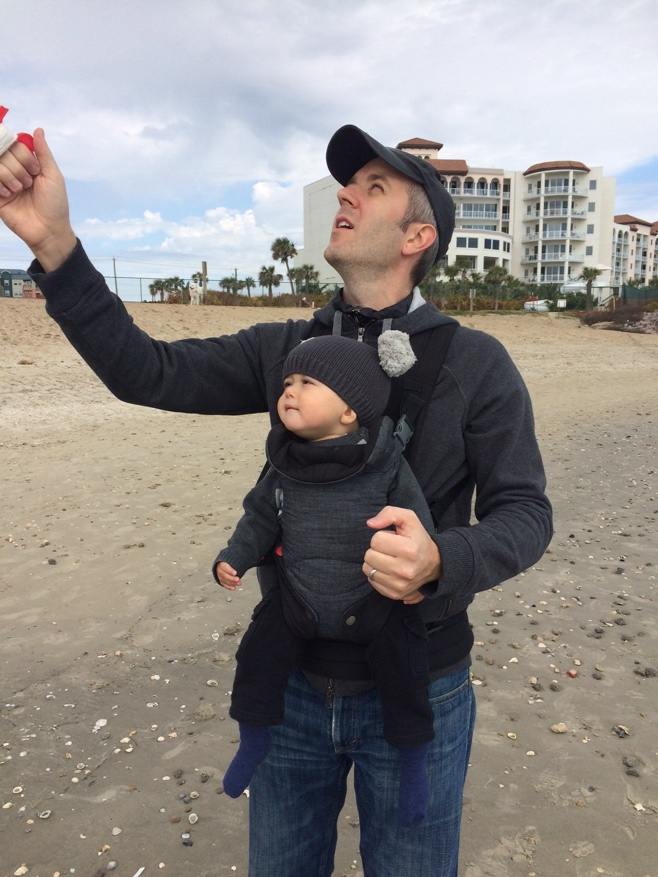 Dad and baby in carrier flying a kite