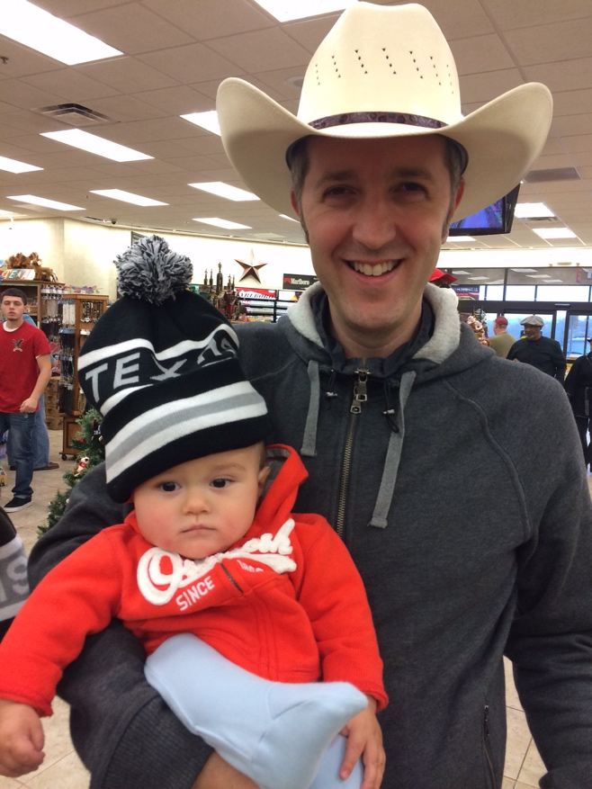 Dad with cowboy hat and baby with Texas hat