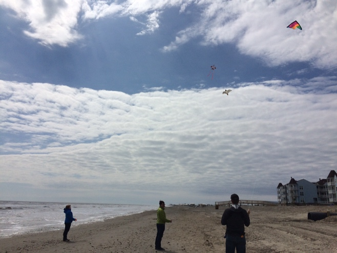 Three adults flying kites on the beach