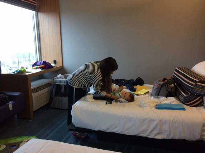 Babysitter changing baby in hotel room