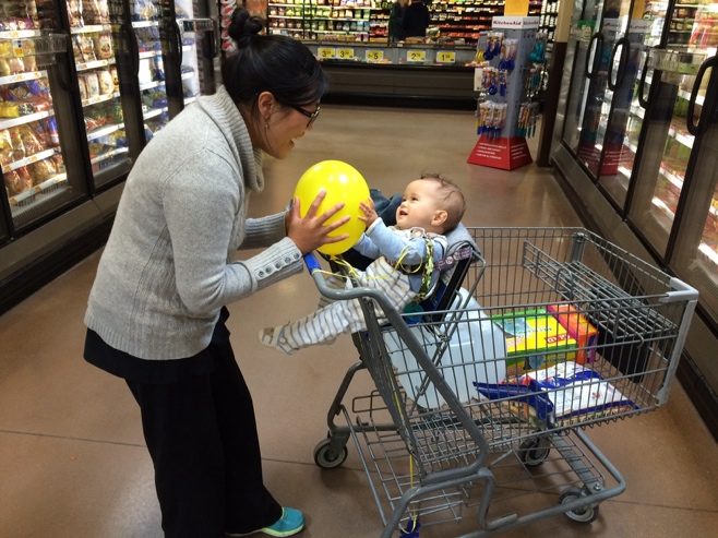 Baby and mum with yellow balloon in supermarket