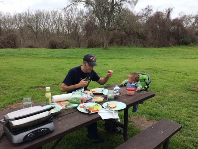 Man and baby eating lunch on picnic table