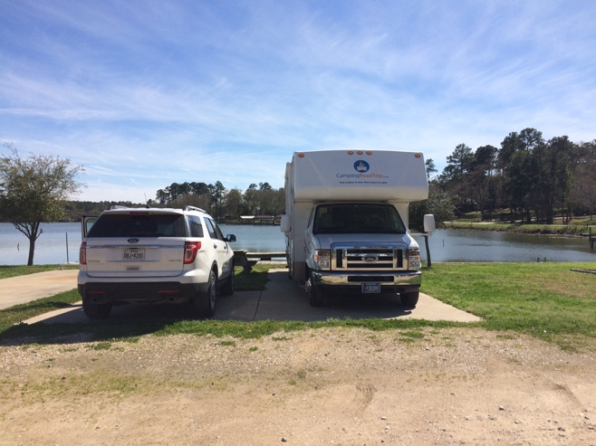 White car parked next to RV with lake in background