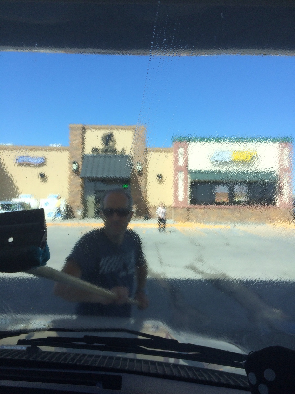 English hubby cleaning windscreen