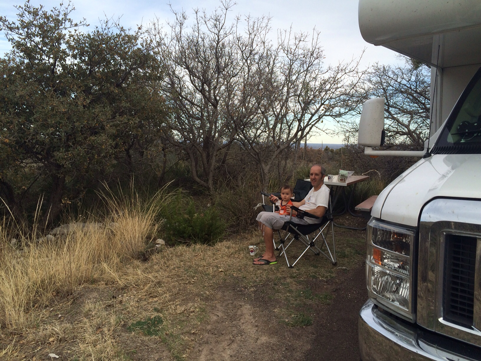 Baby boy o and dad sitting in camping chair outside RV