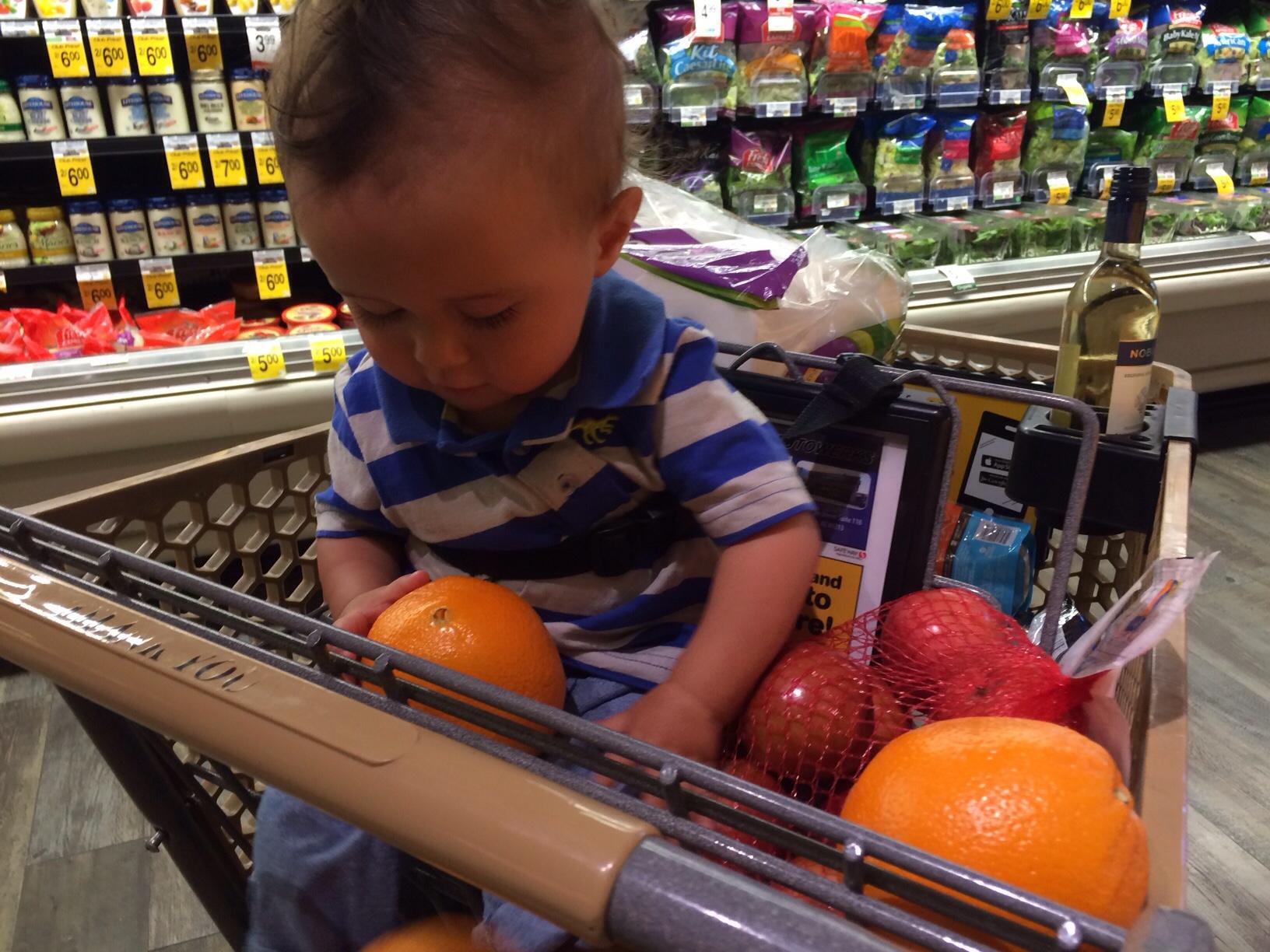 Baby boy o holding oranges