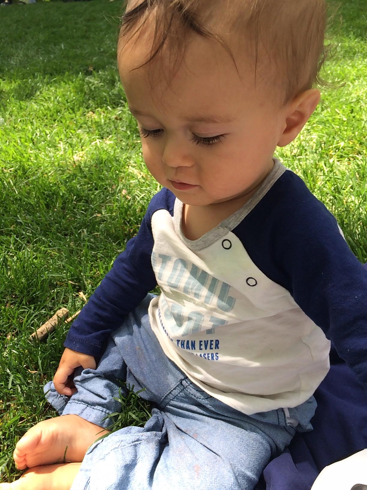 Baby boy o sitting on grass