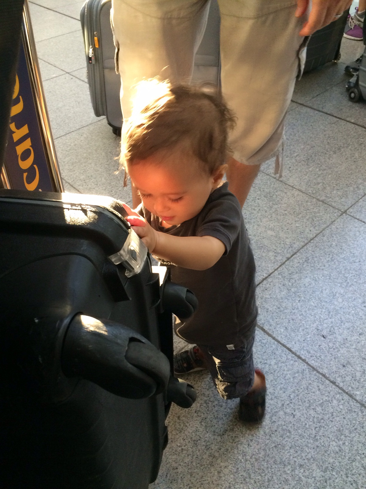 Baby boy o pushing luggage