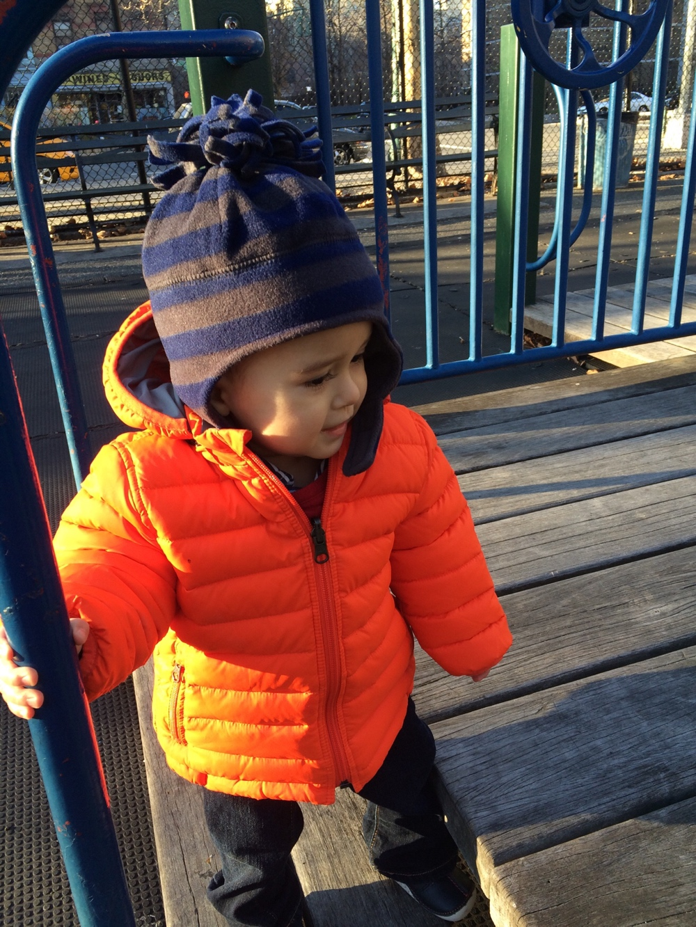Baby in orange puffer jacket at park