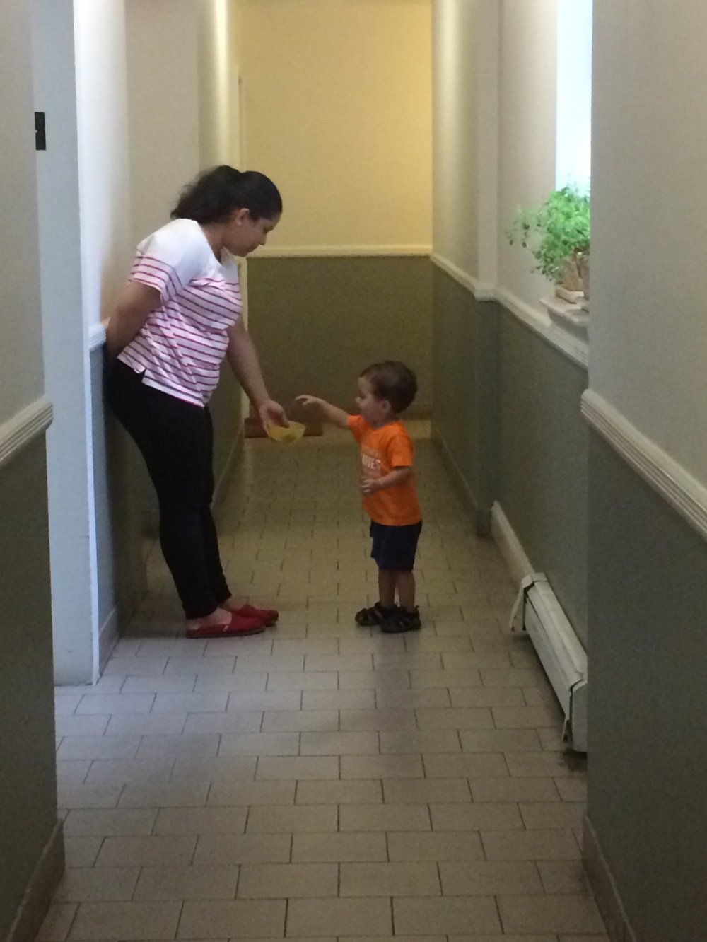 Toddler with nanny in hallway